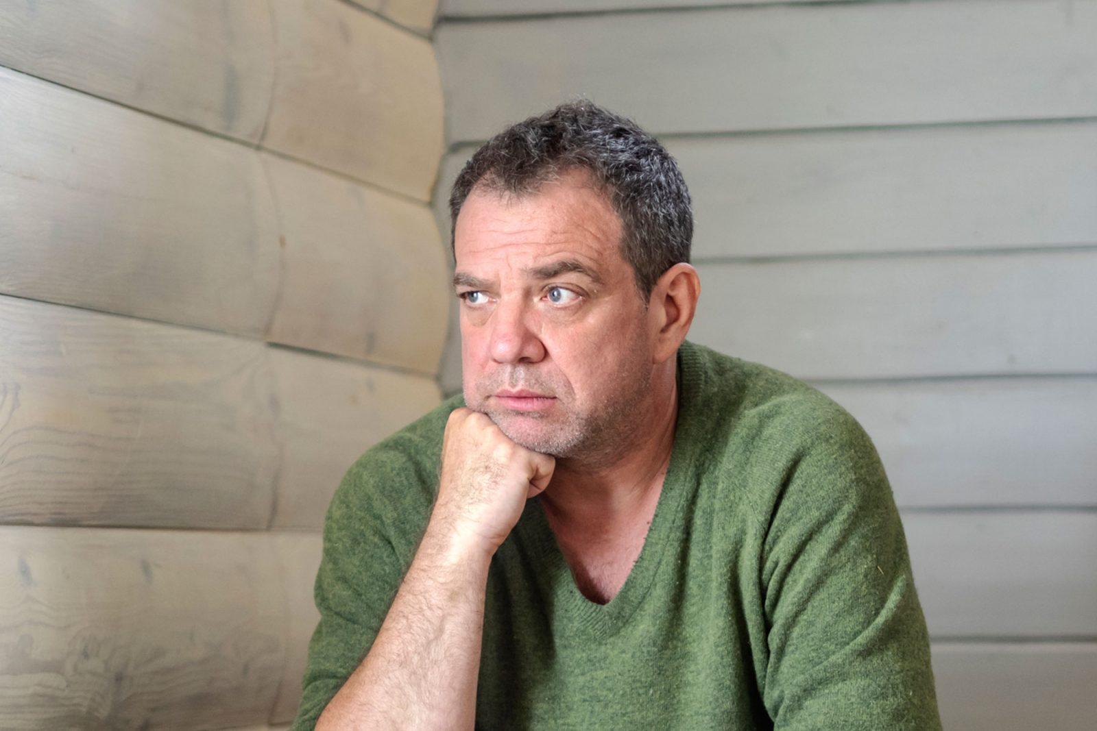 Man sat in a room looking sad